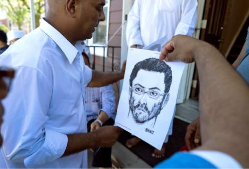 At the front entrance of the Al-Furqan Jame Masjid mosque in the Ozone Park section of Queens, a police sketch of a suspect believed to have shot the mosque's Imam is handed out by members of the mosque Sunday, Aug. 14, 2016, a day after 55-year-old Imam Maulama Akonjee and his 64-year-old associate, Thara Uddin, were shot in the back of the head after they left the mosque following afternoon prayers Saturday. (AP Photo/Craig Ruttle)