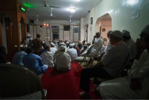 In this Saturday, Aug. 13, 2016, photo, people gather inside the Al-Furqan Jame Masjid mosque in the Ozone Park section of Queens, not far from the crime scene where the leader of the mosque and an associate were fatally shot in a brazen daylight attack as they left afternoon prayers Saturday. Police said 55-year-old Imam Maulama Akonjee and his 64-year-old associate, Tharam Uddin, were shot in the back of the head as they left the mosque shortly before 2 p.m. (AP Photo/Craig Ruttle)
