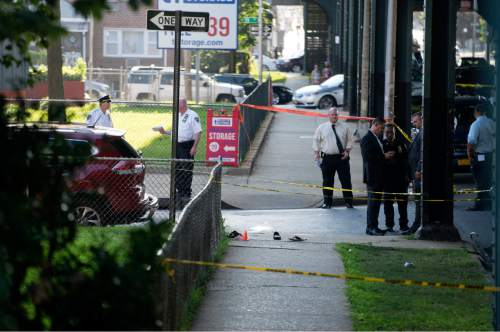 Sandals lay on a street corner at the crime scene, Saturday, Aug. 13, 2016, not far from the Al-Furqan Jame Masjid Mosque in the Ozone Park neighborhood of Queens, New York, where the leader of a New York City mosque has been fatally shot and an associate has been wounded in a brazen daylight attack. (AP Photo/Craig Ruttle)