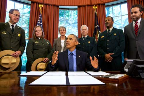 FILE - In this July 10, 2015, file photo, President Barack Obama, center, talks about the designation of three new national monuments; Berryessa Snow Mountain in California, Waco Mammoth in Texas, and the Basin and Range in Nevada, in the Oval Office of the White House in Washington. Behind him from left are Victor Knox, associate director of park planning, facilities and lands of the National Park Service; April Slayton, chief of public affairs and chief spokesperson of the National Park Service; Secretary of the Interior Sally Jewell; U.S. Forest Service Chief Tom Tidwell; Randy Moore, Forest Service; and Bureau of Land Management director Neil Kornze. The race is on to win Obama's attention as he puts some final touches on his environmental legacy. Conservation groups, American Indian tribes and lawmakers are pushing him to preserve millions of acres as national monuments. That designation often prevents new drilling and mining on public lands, or the construction of new roads and utility lines. (AP Photo/Jacquelyn Martin, File)