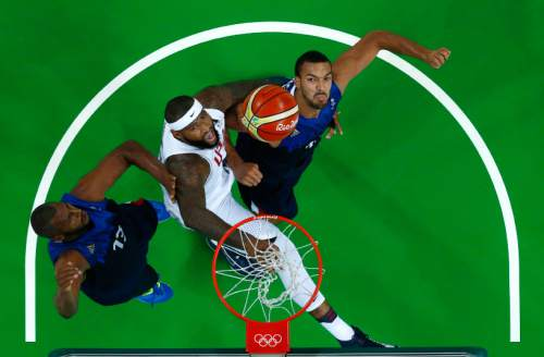 United States' DeMarcus Cousins (12) fights for a rebound with France's Boris Diaw, left, and Rudy Gobert, right, during a basketball game at the 2016 Summer Olympics in Rio de Janeiro, Brazil, Sunday, Aug. 14, 2016. (Jim Young/Pool Photo via AP)