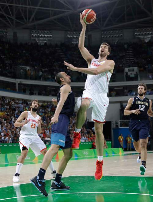 Spain's Pau Gasol (4) shoots over Argentina's Manu Ginobili (5) during a men's basketball game at the 2016 Summer Olympics in Rio de Janeiro, Brazil, Monday, Aug. 15, 2016. (AP Photo/Eric Gay)