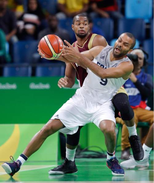 France's Tony Parker (9) tires to work the ball around Venezuela's David Cubillan (8) during a men's basketball game at the 2016 Summer Olympics in Rio de Janeiro, Brazil, Friday, Aug. 12, 2016. (AP Photo/Eric Gay)