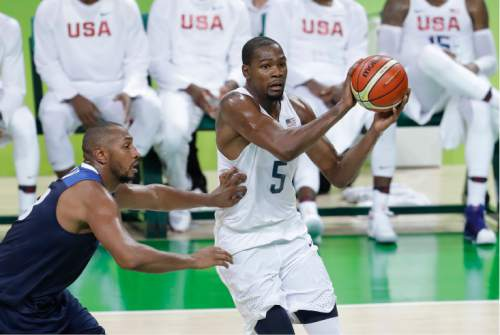 """FILE - In this Aug. 14, 2016 photo, United States' Kevin Durant (5) works the ball around France's Boris Diaw, left, during a men's basketball game at the 2016 Summer Olympics in Rio de Janeiro, Brazil. The U.S. men's basketball team, which has won 50 straight international tournament games, is still adjusting to the different style of play in Rio. There are 10 first-time Olympians on that squad, which has been challenged in the tournament. The men are 5-0, but won each of their last two games by three points. """"It's slower. Teams try to slow the game down,"""" Kevin Durant said of one of the many differences between the NBA and international play.  (AP Photo/Eric Gay, File)"""