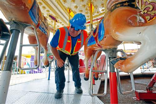 In this Tuesday, Oct. 6, 2015 file photo, amusement device inspector Avery Wheelock inspects the safety pins on a children's merry-go-round at the Mississippi State Fair in Jackson, Miss. In some parts of the U.S., the thrill rides that hurl kids upside down, whirl them around or send them shooting down slides are checked out by state inspectors before customers climb on. But in other places, they are not required to get the once-over. (AP Photo/Rogelio V. Solis, File)