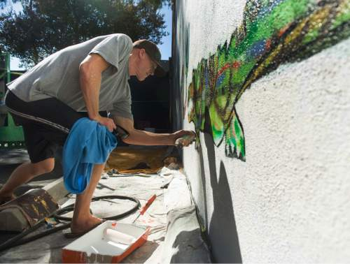 FILE - In this Sept. 26, 2014, file photo, Todd Marinovich, the former Orange County high school, USC and NFL quarterback whose career was derailed by drug addiction, paints a mural on the side of the Gem Theatre in Garden Grove, Calif. Marinovich has been arrested after being found naked with marijuana and possibly methamphetamine in a stranger's backyard in Southern California. Irvine Police Cmdr. Mike Hallinan said Monday, Aug. 22, 2016, that Marinovich was arrested Friday night, Aug. 19, after a call saying a naked man was on a hiking trail near homes. The officers found him in a backyard holding a brown bag containing marijuana and a substance that appeared to be meth but police are awaiting lab results. (Kevin Sullivan/The Orange County Register via AP, File)
