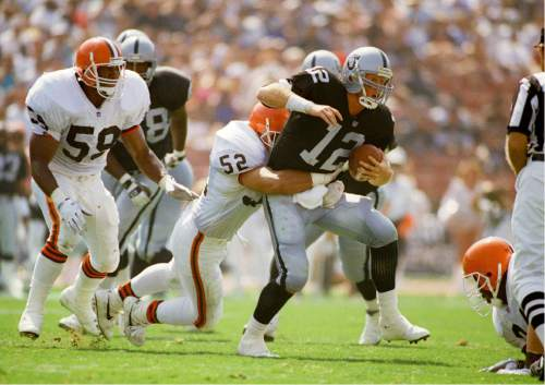 FILE - In this Sept. 20, 1992, file photo, Los Angeles Raiders starting guard quarterback Todd Marinovich (12) runs out of the pocket and is tackled by Cleveland Browns linebacker Richard Brown (52) during second quarter action in Los Angeles. Marinovich has been arrested after being found naked with marijuana and possibly methamphetamine in a stranger's backyard in Southern California. Irvine Police Cmdr. Mike Hallinan said Monday, Aug. 22, 2016, that Marinovich was arrested Friday, Aug. 19, after a call saying a naked man was on a hiking trail near homes. (AP Photo/Kevork Djansezian, File)