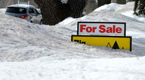 """FILE - In this Feb. 24, 2015 file photo, a """"For Sale"""" sign pokes out of about 4 feet of snow in the front yard of a home listed in Derry, N.H. The National Association of Realtors releases existing home sales for February on Monday, March 23, 2015. (AP Photo/Charles Krupa, File)"""
