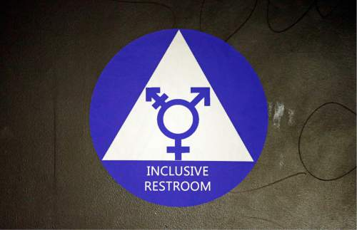 FILE - In this May 17, 2016, file photo, a new sticker designates a gender neutral bathroom at Nathan Hale high school in Seattle. A federal judge in Texas is blocking for now the Obama administration's directive to U.S. public schools that transgender students must be allowed to use the bathrooms and locker rooms consistent with their chosen gender identity. (AP Photo/Elaine Thompson, File)