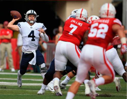 BYU quarterback Taysom Hill (4) throws under pressure from Nebraska defensive tackle Maliek Collins (7) and linebacker Josh Banderas (52) during the first half of an NCAA college football game in Lincoln, Neb., Saturday, Sept. 5, 2015. (AP Photo/Nati Harnik)