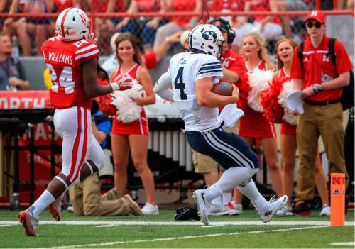 BYU quarterback Taysom Hill (4) is chased by Nebraska safety Aaron Williams (24) as he runs for a touchdown during the first half of an NCAA college football game in Lincoln, Neb., Saturday, Sept. 5, 2015. (AP Photo/Nati Harnik)