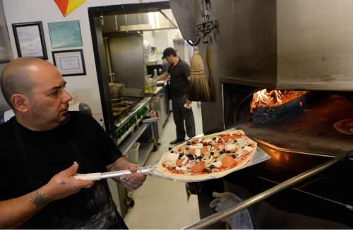 Al Hartmann  |  The Salt Lake Tribune  Pizza chef Gaetano Cuttaia slides a pizza into the 700-degree, wood-fired oven for a 3-minute flash cooking at Sicilia Mia, a new fine-dining Italian restaurant in Millcreek.