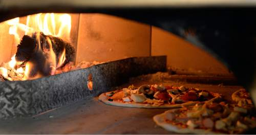 Al Hartmann  |  The Salt Lake Tribune   Pizzas cook in the 700-degree, wood-fired oven at Sicilia Mia, a new Italian restaurant in Millcreek.