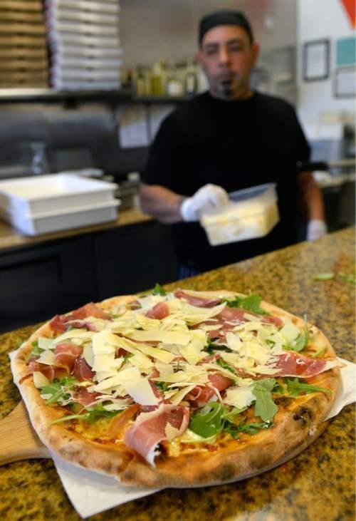 Al Hartmann  |  The Salt Lake Tribune  Sicilia Mia pizza made with mozzarela, arugula, prosciutto, shaved parmesean and olive oil comes out of the the 700-degree wood-fired  at Sicilia Mia in Millcreek.