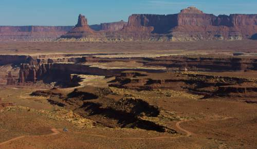 Francisco Kjolseth  |  The Salt Lake Tribune A four-wheel drive car travels the road popular with mountain bikers that makes up the White Rim trail in Canyonlands.
