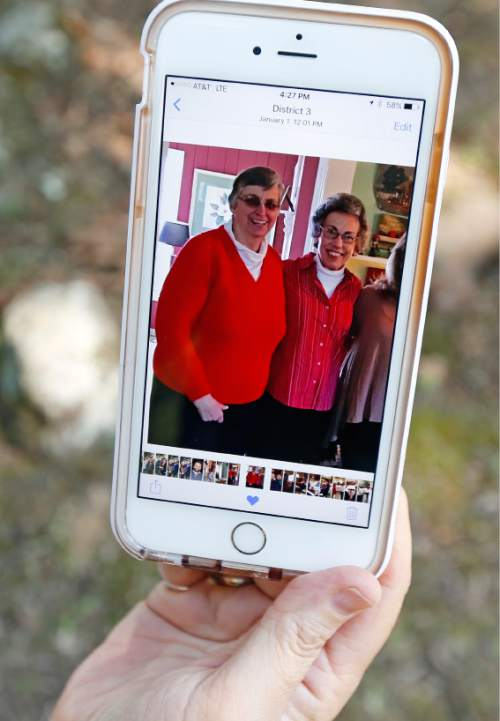 Jamie Sample, a parishioner of St. Thomas the Apostle Catholic Church in Lexington, Miss., sits in the shade in Durant, Miss., and shows a smartphone photograph taken last December 2015, of Sisters Paula Merrill, left, and Margaret Held. The two nuns who worked as nurses, and lived in Durant, Miss., were found slain in their home Thursday, Aug. 25, 2016. There were signs of a break-in and their vehicle was missing. (Courtesy Sample family via AP)