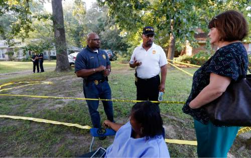 Durant Police Chief John Haynes, left, and assistant Police Chief James Lee reassure Lexington Medical Clinic employees Lisa Dew, right, and Viola Turner, seated, that the Mississippi Bureau of Investigation was giving the home of two slain Catholic nuns who worked as nurses at the clinic a through crime scene investigation, Thursday, Aug. 25, 2016, in Durant. The clinic office manager and a Durant police officer discovered their bodies inside the house after both nuns did not report for work. Authorities said there were signs of a break-in and their vehicle was missing. (AP Photo/Rogelio V. Solis)