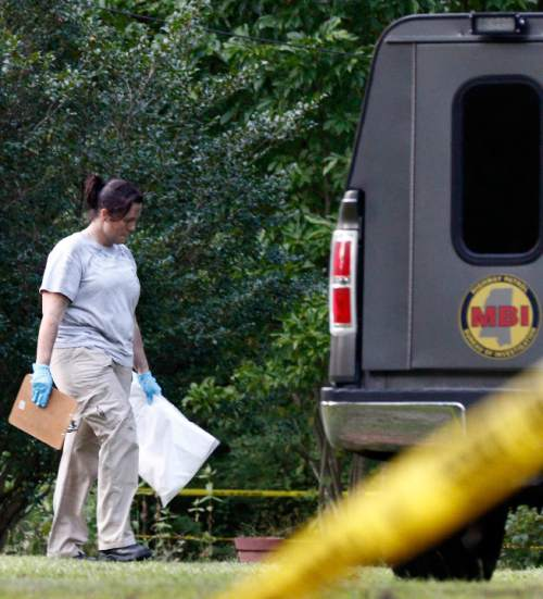 A Mississippi Bureau of Investigation agent takes a bag with evidence from the Durant, Miss., home of two slain Catholic nuns who worked as nurses at the Lexington Medical Clinic, to her vehicle, Thursday, Aug. 25, 2016. The clinic office manager and a Durant police officer discovered their bodies inside the house after both nuns did not report for work. Authorities said their were signs of a break-in and their vehicle was missing. (AP Photo/Rogelio V. Solis)