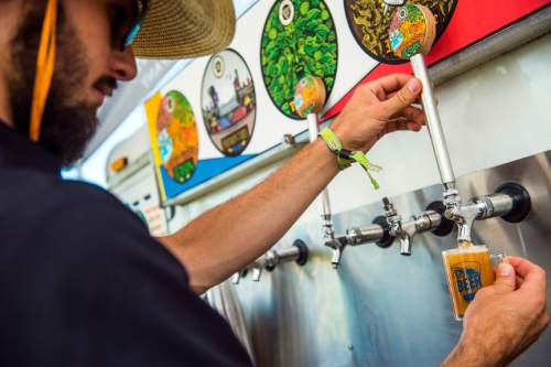 Chris Detrick  |  The Salt Lake Tribune Talisman Brewing Company Assistant Brewer Cade Wight pours beer during the 7th annual Utah Beer Festival at the Utah State Fair Park Saturday August 27, 2016. The festival featured over 150 different beers and ciders.