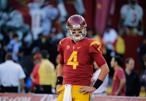 In this Oct. 8, 2015 photo, Southern California quarterback Max Browne warms up before an NCAA college football game against Washington in Los Angeles. Southern California's quarterback competition will continue in fall training camp after coach Clay Helton was unable to choose a winner in spring practice. Helton announced his decision to extend the competition Monday, April 18, 2016. Browne, a USC junior, and redshirt freshman Sam Darnold are the front-runners in the Trojans' second true quarterback competition since 2009. (AP Photo/Jae C. Hong)