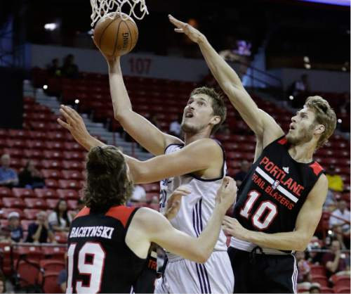 Utah Jazz's Tibor Pleiss, center, shoots over Portland Trail Blazers' Jordan Bachynski, left, and Jake Layman during the second half of an NBA summer league basketball game Wednesday, July 13, 2016, in Las Vegas. (AP Photo/John Locher)