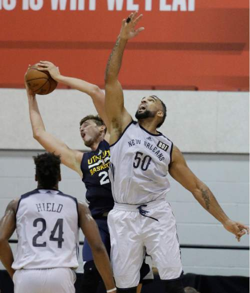 New Orleans Pelicans' Liam McMorrow, right, battles for a rebound with Utah Jazz's Tibor Pleiss during the second half of an NBA summer league basketball game, Sunday, July 10, 2016, in Las Vegas. (AP Photo/John Locher)