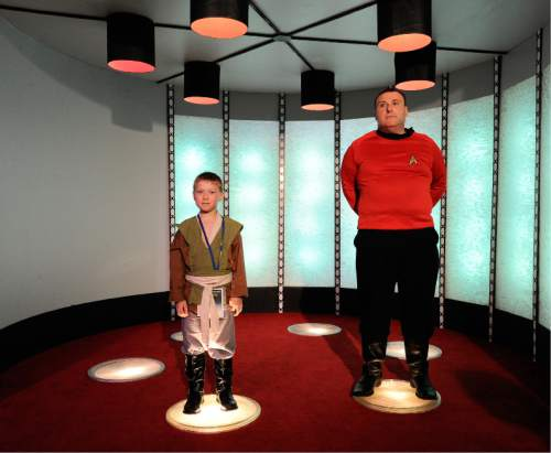 "In this Saturday, Aug. 13, 2016 photo, Cooper Marchese, 7, dressed as a ""Star Wars ""Jedi Knight and his father Carl Marchese dressed as a ""Star Trek"" crew member both of Baltimore, Md., stand in the transporter room while taking a tour of a replica of the original ""Star Trek"" series starship Enterprise during the Trekonderoga festival in Ticonderoga, N.Y. (AP Photo/Hans Pennink)"