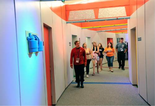 "In this Saturday, Aug. 13, 2016 photo, tour guide Willie Yee, left, of New Paltz, N.Y., leads a guided tour of a replica of the ""Star Trek"" Enterprise during the Trekonderoga festival in Ticonderoga, N.Y. Sets mimicking those of the 1960s TV series ""Star Trek"" have become a tourist attraction in upstate New York. They were lovingly built by fans in recent years for an internet film series produced in the town of Ticonderoga. (AP Photo/Hans Pennink)"