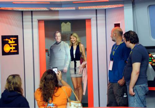 "In this Saturday, Aug. 13, 2016 photo, Kara Benoit of Frederick, Md., poses for a photograph with a cardboard cutout of Capt. James T. Kirk in the turbo lift entrance to the bridge of the replica starship Enterprise during the Trekonderoga festival in Ticonderoga, N.Y. Sets mimicking those of the 1960s TV series ""Star Trek"" have become a tourist attraction in upstate New York.  (AP Photo/Hans Pennink)"