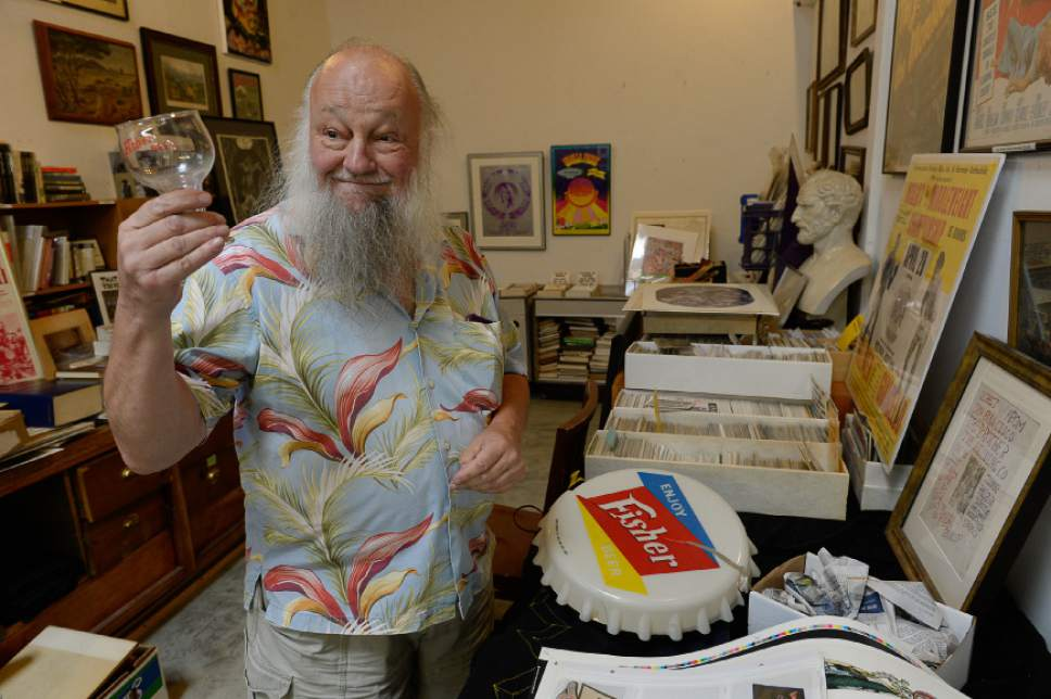 Francisco Kjolseth | The Salt Lake Tribune Ken Sanders of Ken Sanders Rare Books, holds up a Fisher Brewing Co. glass, memorabilia of one of two Utah breweries to have survived Prohibition, until finally disappearing in the 1960s.