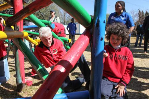FILE - In this Aug. 8, 2015 file photo, former President Bill Clinton helps paint a jungle gym during a visit to a Clinton Foundation project in Johannesburg. As Bill Clinton's presidency ended, he was popular, yet still tainted by scandal, and struggling to find his footing after eight years in the White House. He eventually channeled his energy into the global philanthropy that bears his name and has shaped so much of his post-presidential legacy.  (AP Photo Jordi Matis, File)