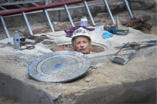 Scott Sommerdorf   |  The Salt Lake Tribune   A worker pops up out of a manhole cover outside Martine Restaurant near Main Street, Wednesday, August 31, 2016. There is currently a shortage of construction workers.
