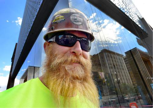 Scott Sommerdorf   |  The Salt Lake Tribune   Construction worker Taylor Thomas passes by 111 high-rise next door to the new  Eccles Theater on Main Street, Wednesday, August 31, 2016.
