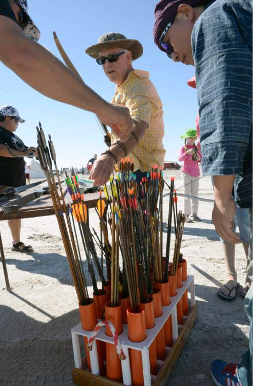 Al Hartmann  |  The Salt Lake Tribune Archers collect their arrows for the first round shoot at the U.S. Flight Archery Association's annual meet on the Salt Flats Friday. It runs through Sunday. This is a big event with international competitors where archers shoot for distance with different classes of bows, from high tech crossbows to traditonal primative wooden bows.  Most are handmade with different pull weights.