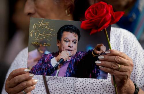 A woman holds a picture of Mexican songwriter and singer Juan Gabriel near a statue of him during a mass in Mexico City's Garibaldi plaza, Tuesday, Aug. 30, 2016. Juan Gabriel, who's real name was Alberto Aguilera Valadez, was an icon in the Latin music world died Sunday, Aug. 29, at his home in California, his publicist said. (AP Photo/Eduardo Verdugo)