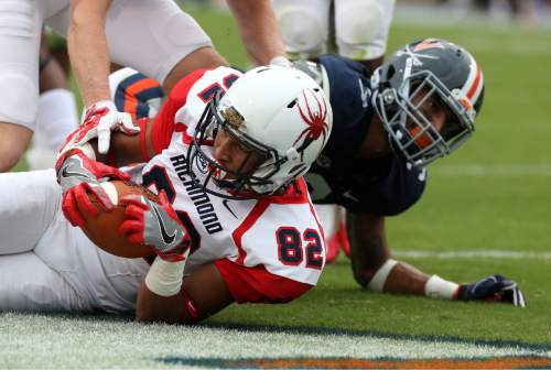 Richmond wide receiver Tyler Wilkins (82) scores a touchdown in front of Virginia safety Kelvin Rainey (38) during the first half of an NCAA football game Saturday Sept. 3, 2016, in Charlottesville, Va. (AP Photo/Andrew Shurtleff)