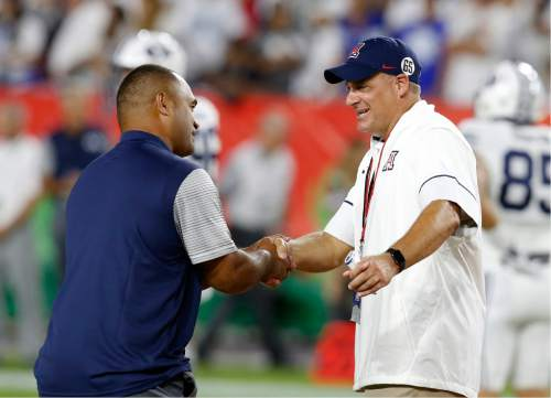 BYU running backs coach Reno Mahe, left, and Arizona coach Rich Rodriguez talk before an NCAA college football game, Saturday, Sept. 3, 2016, in Phoenix. (AP Photo/Rick Scuteri)