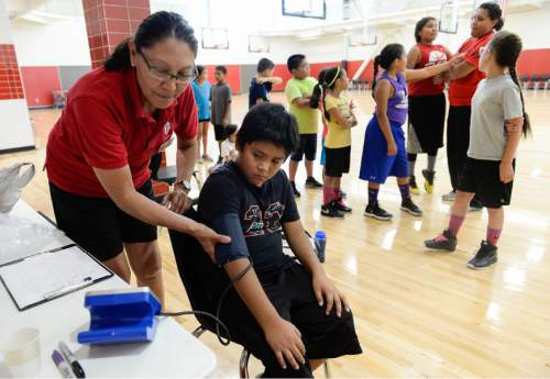 Francisco Kjolseth | The Salt Lake Tribune American Indian Navajo Ely Whiterock, 9, gets a blood pressure check from Certified Personal Trainer Gay Dawn Pinnecoose as part of a diabetes prevention program used to fund a basketball camp for mixed race students.