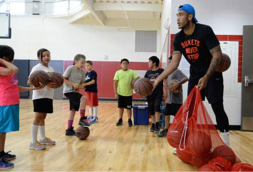 Francisco Kjolseth | The Salt Lake Tribune American basketball star Damen Bell-Holter hands out basketballs to American Indian students as they participate in a self-esteem-boosting basketball program run by the Urban Indian Center, for youths grade 4 to 6. The program held at Mt Jordan Middle School in Sandy was a rare opportunity for kids that normally fall through the cracks for funding.