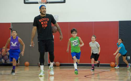 Francisco Kjolseth | The Salt Lake Tribune American basketball star Damen Bell-Holter towers over American Indian students as they participate in a self-esteem-boosting basketball program run by the Urban Indian Center, for youths grade 4 to 6.