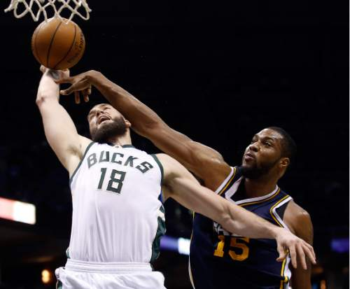 Utah Jazz's Derrick Favors fouls Milwaukee Bucks' Miles Plumlee (18) as he goes up for a shot during the first half of an NBA basketball game Sunday, March 20, 2016, in Milwaukee. (AP Photo/Morry Gash)