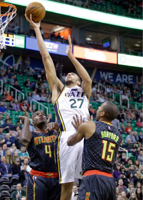 Utah Jazz center Rudy Gobert (27) goes to the basket as Atlanta Hawks' Paul Millsap (4) and Al Horford (15) defend during the first quarter of an NBA basketball game Tuesday, March 8, 2016, in Salt Lake City. (AP Photo/Rick Bowmer)