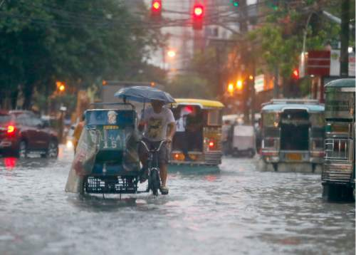 FILE - In this Aug. 26, 2016 file photo, commuters and motorists go on their way as heavy monsoon rains inundate low-lying areas in Manila, Philippines. Typhoons that slam into land in the northwestern Pacific _ especially the biggest tropical cyclones of the bunch _ have gotten considerably stronger since the 1970s, a new study concludes. (AP Photo/Bullit Marquez, File)
