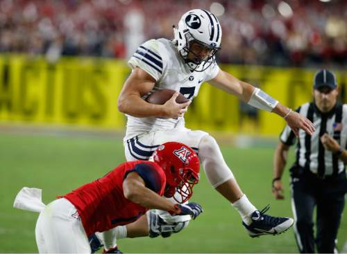 BYU quarterback Taysom Hill (7) leaps over Arizona cornerback Jace Whittaker during the first half of an NCAA college football game, Saturday, Sept. 3, 2016, in Phoenix. (AP Photo/Rick Scuteri)