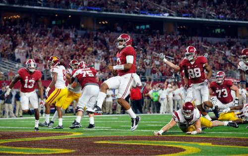 Alabama quarterback Jalen Hurts jumps into the end zone on a 7-yard touchdown run during the second half of an NCAA college football game against Southern California Saturday, Sept. 3, 2016, in Arlington, Texas. (AP Photo/Tony Gutierrez)