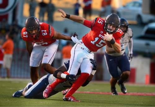 In this Sept. 11, 2015 photo, Utah quarterback Chase Hansen runs with the ball against Utah State at Rice-Eccles Stadium in Salt Lake City. Freshman Chase Hansen is the quarterback of the future for No. 3 Utah, but in the meanwhile, he's switched jerseys and sides of the ball.  (Scott Sommerdorf/The Salt Lake Tribune via AP) DESERET NEWS OUT; LOCAL TELEVISION OUT; MAGS OUT; MANDATORY CREDIT