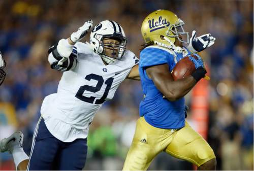 FILE - This Sept. 19, 2015, file photo, BYU linebacker Harvey Langi, left, dives to bring down UCLA running back Paul Perkins, right, on a long gain during the first half of an NCAA college football game, in Pasadena, Calif. Langi was the second-leading tackler for BYU in 2015 and now has been asked to move from linebacker to defensive end in the new 4-3 scheme. The posiitonal switch under the scheme is yet another change under the new coaching staff. (AP Photo/Danny Moloshok, File)