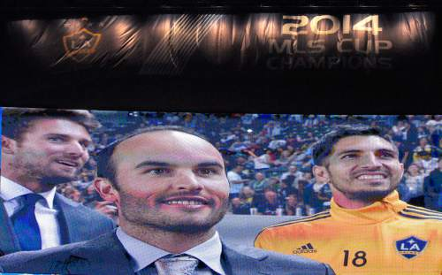 Former Los Angeles Galaxy player Landon Donovan, center, is shown on the big screen as the 2014 MLS Cup championship banner is raised prior to the Galaxy's MLS soccer match against the Chicago Fire, Friday, March 6, 2015, in Los Angeles. Galaxy goalkeeper Jaime Penedo is at right. (AP Photo/Mark J. Terrill)