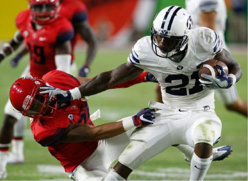 BYU running back Jamaal Williams (21) stiff arms Arizona safety Anthony Mariscal during the second half of an NCAA college football game, Saturday, Sept. 3, 2016, in Phoenix. BYU defeated Arizona 18-16. (AP Photo/Rick Scuteri)