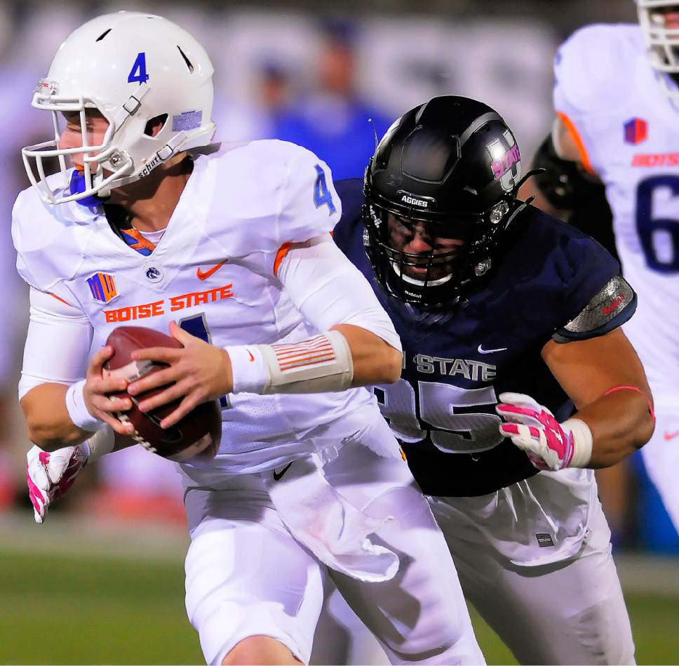 Boise State quarterback Brett Rypien (4) gets sacked by Utah State defensive end Ricky Ali'ifua (95) during an NCAA college football game Friday, Oct. 16, 2015, in Logan, Utah. (Eli Lucero/The Herald Journal via AP)